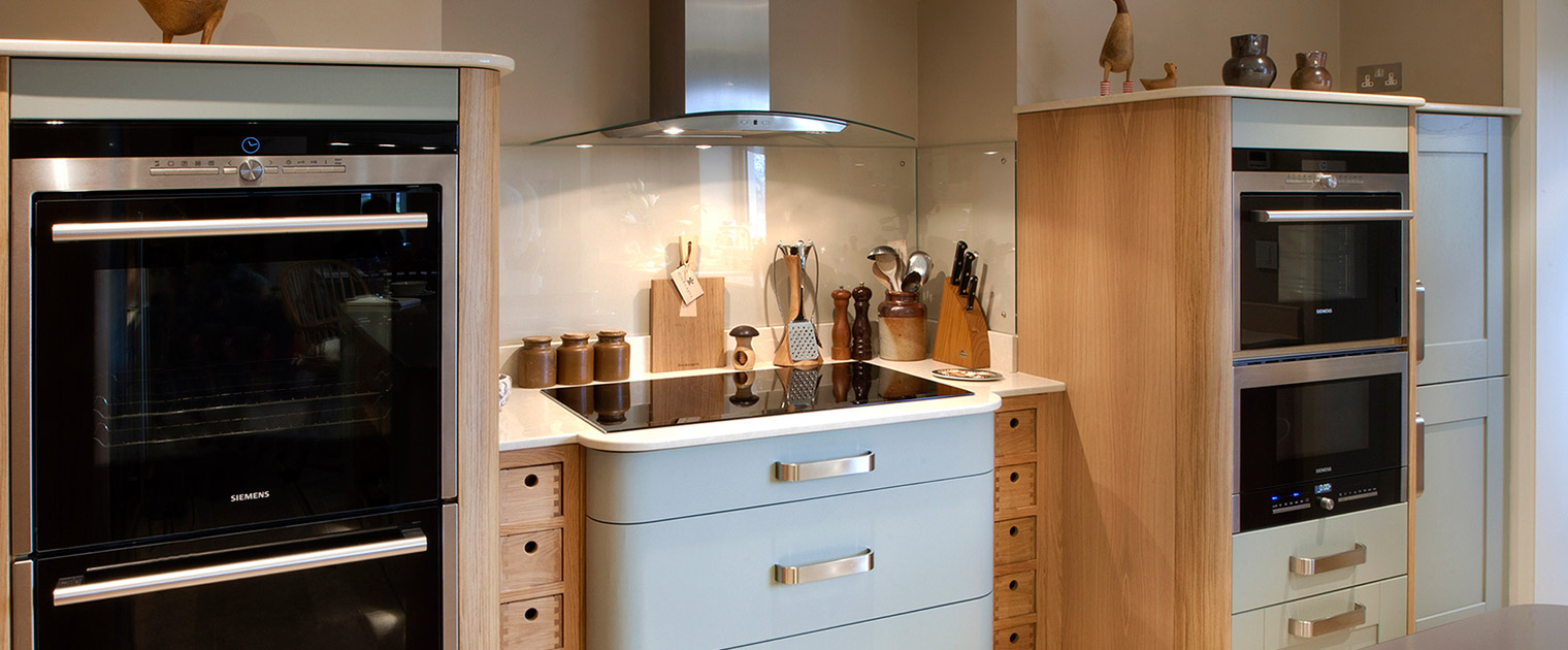 Deco rounded kitchen units in elephants breath and oak with dual ovens integrated appliances and induction hob