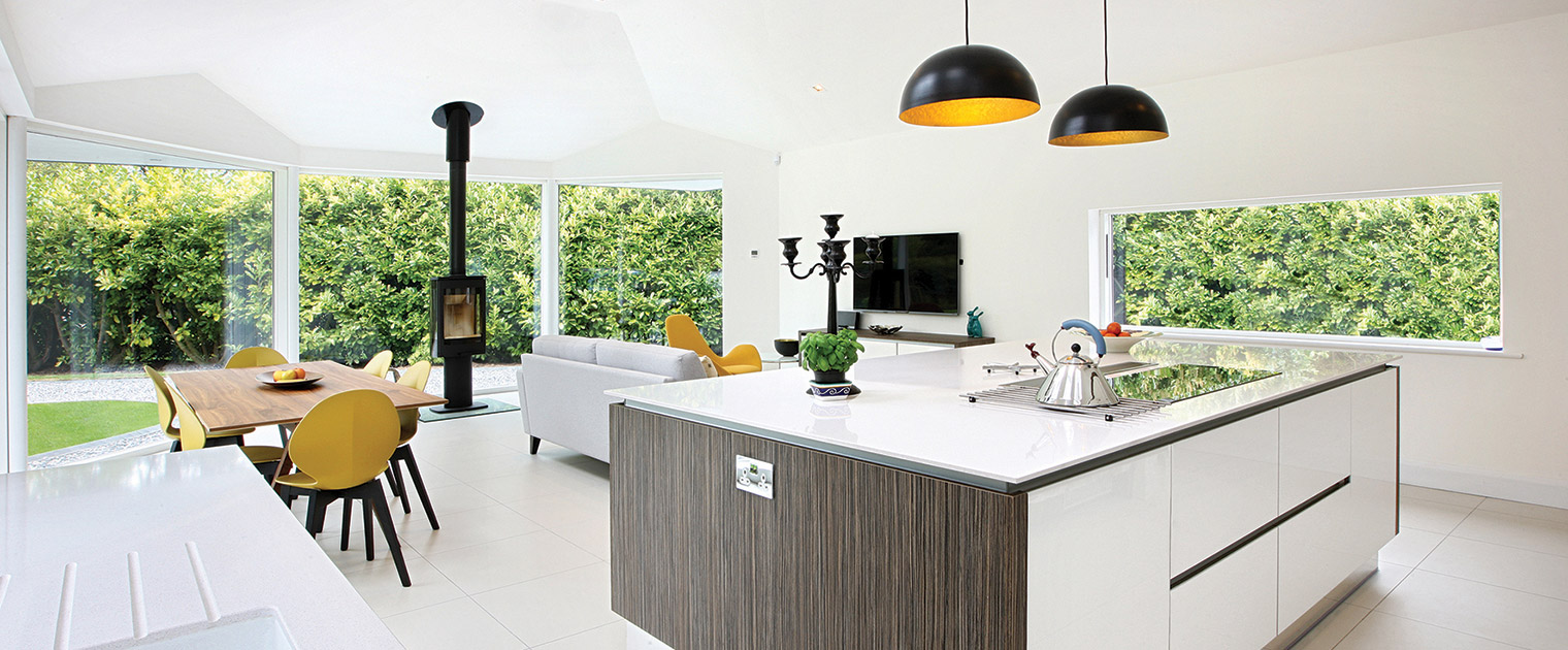 Modern new build open plan white kitchen with island, induction hob, pendant lighting, blanco norte Silestone worktop