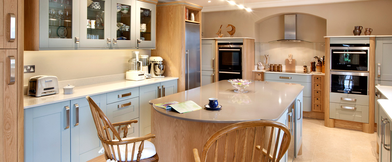 Traditional family kitchen with island, vintage breakfast bar stools and glass display cabinets