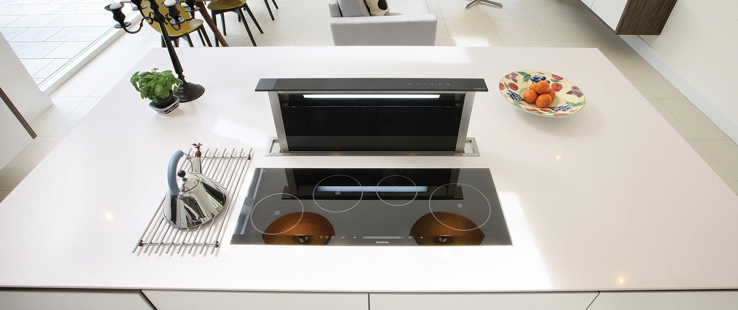 modern white open plan kitchen with induction hob and pop up extractor
